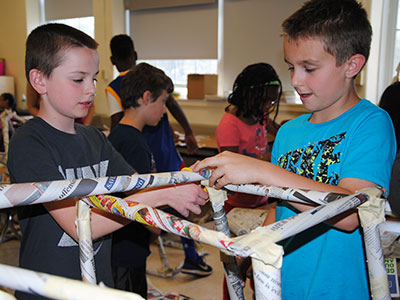 Two students work with newspaper to build a structure.