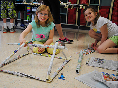 Two Park Avenue students build a solid structure with newspaper.