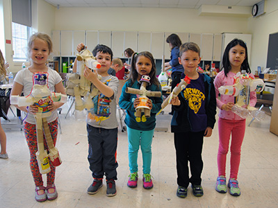 Five Park Avenue kindergarten students display their creations made from recyclables.