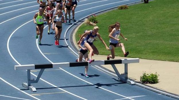 Photo of Megan Reilly jumping a hurdle