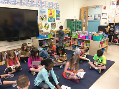 Group of students reading on rug