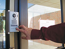 photo of a person pressing a door buzzer at school entrance