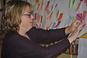 Photo of teacher putting post-it-note on board.