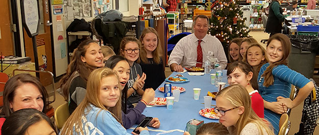 Students and a teacher sit around a table eating together.