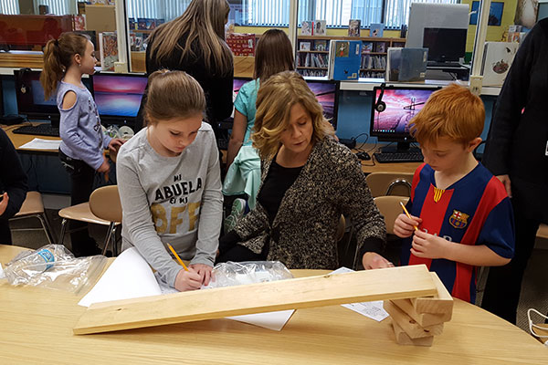 teacher works with students to construct simple machines
