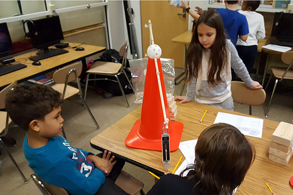 students work together to solve a problem with simple machines