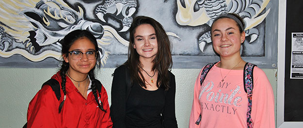 Three high school female students pose in front of a mural