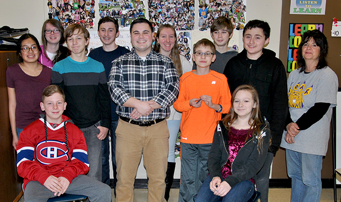 Middle School teacher Mark Botta poses with a group of his students