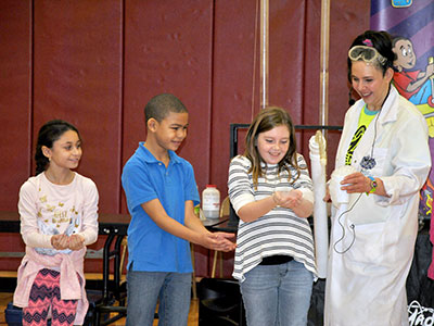 Mad Science presenter places foam in the hands of volunteer students