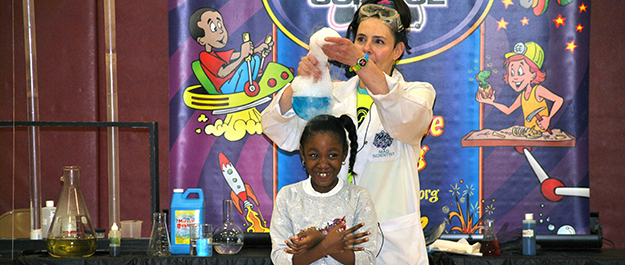 Sanfordville student waits for Mad Science presenter to drop foam on her hair
