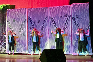 A scene from Sanfordville's Shrek Jr. production: four characters in rags are fastened to chains from their wrists.
