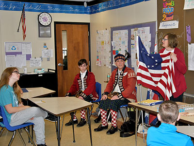 Seventy grade class learns about the American Revolution through guest-educator and war reenactors.