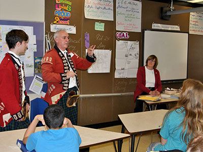 Revolutionary war reenacotrs show a musket ball to a class of seventh graders.