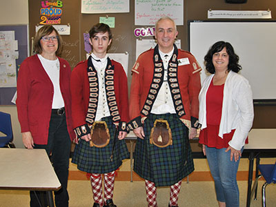 Two Revolutionary War reenactors pose with guest-educator and middle school teacher.