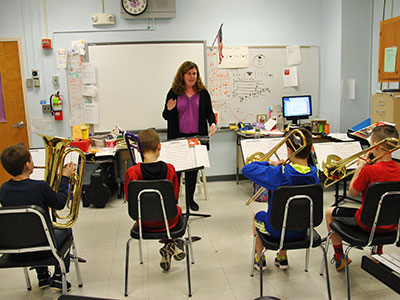Band teacher directs four students playing brass instruments.