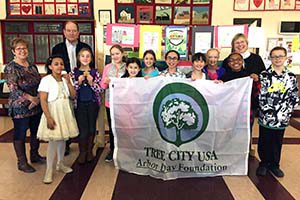 """Poster contest participants pose holding the """"Tree City USA"""" flag during a reception at Town Hall."""