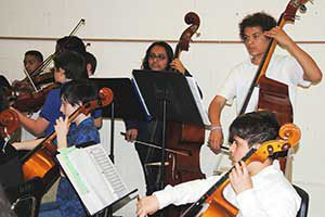 Middle school students in the string section of the orchestra paly cellos and violins.