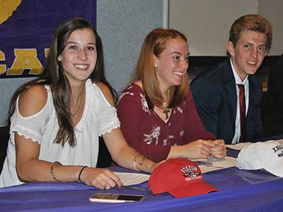 Three student athletes who signed letters of intent sit at signing table with hats branded with the logos of their colleges of choice