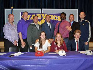 Three student athletes who signed letters of intent pose with their coaches
