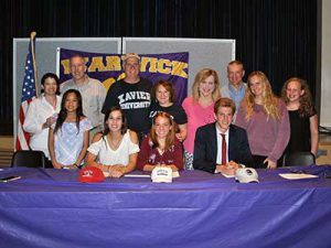 Three student athletes who signed letters of intent pose with their families
