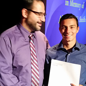 High school administrator presents award to student