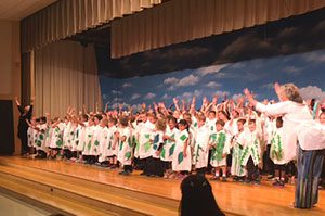 A large group of Sanfordville students fill the stage and raise their arms as part of their dance performance. Mrs. Mensch is seen at the right end of the stage directing the group.
