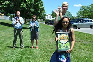 Sarah Werner, winner of the NYSDEC poster contest pose with her poster during a tree planting ceremony.