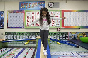 A female kindergarten student balances on a beam