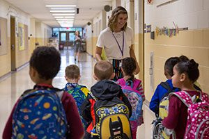 An elementary teacher leads her students down the hall.