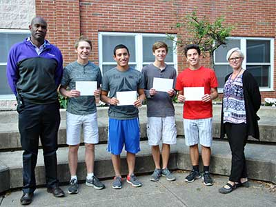 Four high school students pose with their principal and school counselor, holding letters of commendation.