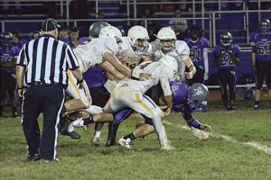 Warwick football players tackle a Valley Central player as a referee observes the play