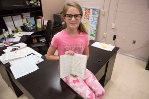 Molly Hewitt sits on the principal's desk and displays her Book of Kindness