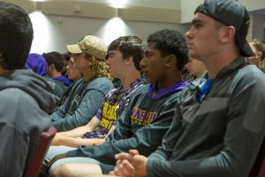 Student athletes seated in auditorium seats