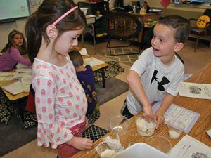 A student mixing play dough talks with team member.