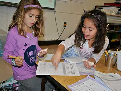 Two students score the performance of their play dough product on a usage test table.
