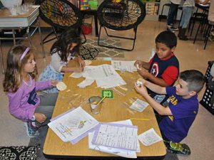 Four students work on their play dough improvement process.