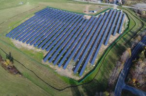 An aerial image of the solar power project, showing the entire solar field framed by green grass and trees.