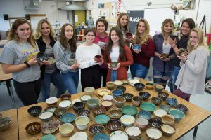 Members of the Empty Bowls Club display pottery