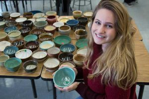 A female student displays pottery bowls