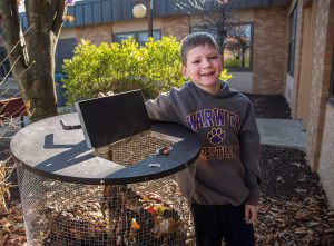 A elementary boy lifts the lid of a compost bin in a school garden.
