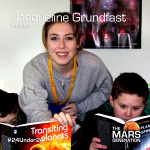 A  female high school senior in a grey sweat shirt and a younger student read a book about space together.