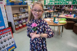 A second grade girl in a floral dress, holding a pink rose and bracelets she designed