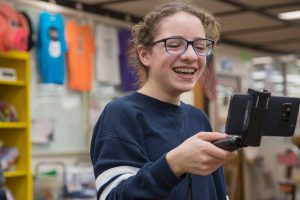 A female middle school student looks into a cell phone on a selfie stick