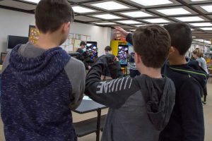 Three male students look into a smart phone to experience augmented reality