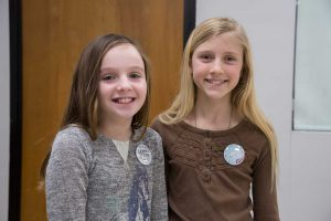 Two Middle School Girls stand side by side wearing the buttons they designed