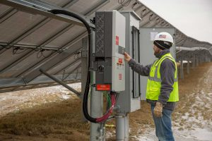 A man in a hard hat inspects a solar project control board