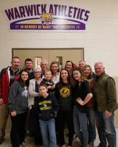 Members of the Mezzetti family  pose for a photo under the new entrance sign to the high school gym.