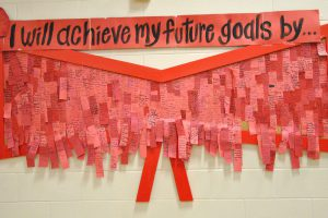 "A wall banner titled, ""I will achieve my future goals by..."" The banner is made up of tens of small red peices of paper with individual pledges from students."