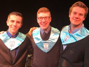 three high school males in blue NHS bibs