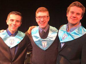 three high school males in blue NHS bibs